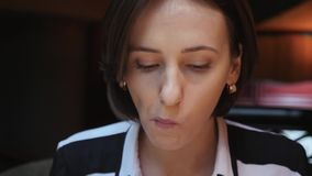 Young attractive business woman is having lunch in a cozy restaurant. Eating vegetarian salad and drinking coffee. Close up view.  stock video