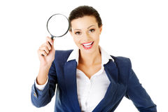 Young attractive business woman looking into a magnifying glass Royalty Free Stock Photos