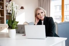 Young attractive business woman in office. Portrait of a young business woman using laptop at office Royalty Free Stock Photos