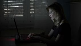 Young attractive business woman sitting at her desk in a dark room typing and chatting with clients on laptop - stock footage