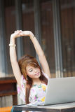 Young attractive business woman tired and stretching on her lapt Royalty Free Stock Photography