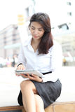 Young attractive business woman uses a mobile tablet computer wi Stock Photography
