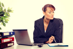 Young attractive business woman using laptop at the office Royalty Free Stock Images