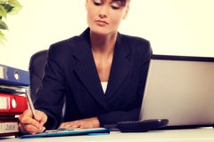 Young attractive business woman using laptop at the office Stock Photos
