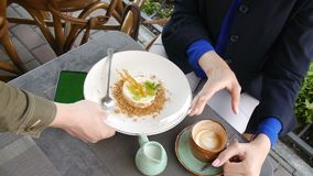 Young attractive business woman using mobile phone with green screen in cafe. The waiter brings a cheesecake. A cup of. Coffee on the table. Red haired woman in stock video