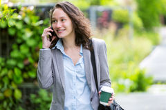 Young attractive business woman walking in the park, with phone Stock Photo