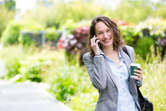 Young attractive business woman walking in the park, with phone Stock Photos