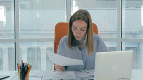 Young attractive business woman working with computer, papers in office. stock footage