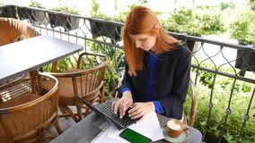 Young attractive business woman using laptop in cafe. Documents, mobile phone with green screen and cup of coffee on the stock footage