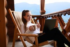 Young attractive business woman is working on the laptop at mountain resort with a cup of tea and cookie. Female relaxes. Young attractive woman is working on Royalty Free Stock Images