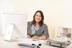 Young attractive business woman working at office. With computer Royalty Free Stock Photo