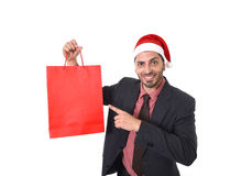 Young attractive businessman in Christmas Santa hat holding and pointing red shopping bag in December and New year sale Royalty Free Stock Photos