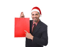 Young attractive businessman in Christmas Santa hat holding and pointing red shopping bag in December and New year sale Royalty Free Stock Images