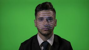 Young attractive businessman with code on face working as a computer programmer on green screen background - stock video footage