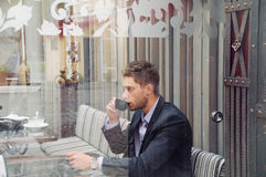 Young attractive businessman drinking espresso coffee in the cit Royalty Free Stock Photography