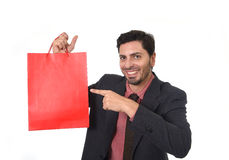 Young attractive businessman holding and pointing red shopping bag in sale concept performing as salesman Royalty Free Stock Photos