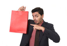 Young attractive businessman holding and pointing red shopping bag in sale concept performing as salesman Royalty Free Stock Photography