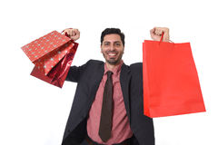 Young attractive businessman holding shopping bags in sale and market opportunity concept Royalty Free Stock Photos