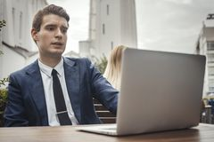 Young attractive businessman sitting next to laptop and looking at monitor. Young attractive businessman sitting at street cafe next to laptop and looking at royalty free stock photos