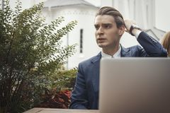 Young attractive businessman sitting next to laptop and touching hair. royalty free stock images