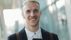 Young attractive businessman standing near business center with smartphone, coffee and headphones. He looking into the stock footage