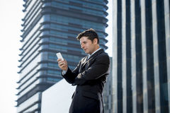 Young attractive businessman in suit and necktie looking text message at mobile phone outdoors Stock Photos