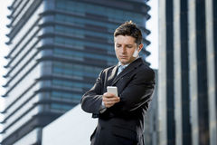 Young attractive businessman in suit and necktie looking text message at mobile phone outdoors Royalty Free Stock Images