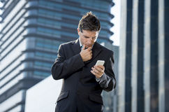 Young attractive businessman in suit and necktie looking text message at mobile phone outdoors Royalty Free Stock Photos