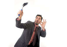 Young attractive businessman in suit and tie taking selfie photo with mobile phone camera and stick posing happy Royalty Free Stock Photography