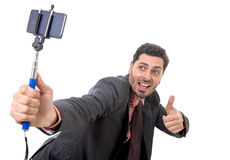 Young attractive businessman in suit and tie taking selfie photo with mobile phone camera and stick posing happy Stock Photos