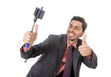 Young attractive businessman in suit and tie taking selfie photo with mobile phone camera and stick posing happy Royalty Free Stock Photos