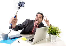 Young attractive businessman in suit and tie taking selfie photo with mobile phone camera and stick posing happy Stock Photo