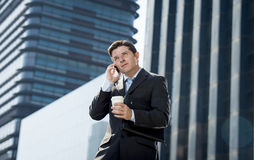 Young attractive businessman in suit and tie talking on mobile phone happy outdoors Royalty Free Stock Images