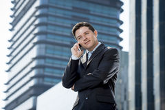 Young attractive businessman in suit and tie talking on mobile phone happy outdoors Stock Photo