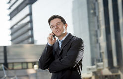 Young attractive businessman in suit and tie talking on mobile phone happy outdoors Royalty Free Stock Photos
