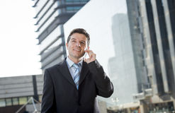 Young attractive businessman in suit and tie talking on mobile phone happy outdoors. Young attractive businessman in suit and necktie talking on mobile smart Stock Images