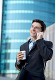 Young attractive businessman in suit and tie talking on mobile phone happy outdoors Royalty Free Stock Photography