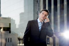 Young attractive businessman in suit and tie talking on mobile phone happy outdoors Stock Photography