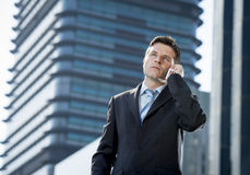 Young attractive businessman in suit and tie talking on mobile phone outdoors Stock Images