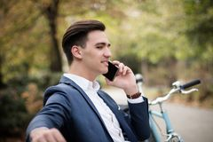 Young businessman talking on smartphone outdoors in the park. A young and attractive businessman talking on his smartphone outdoors in the park Stock Photography