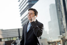 Young attractive businessman talking on mobile phone happy outdoors Stock Images