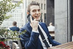 Young attractive businessman talking by mobile phone and looking at viewer. royalty free stock photos