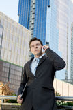 Young attractive businessman talking on mobile phone outdoors Royalty Free Stock Photos