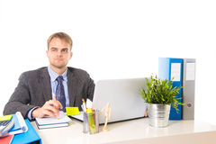 Young attractive businessman working busy with laptop computer holding pen thoughtful smiling Royalty Free Stock Images