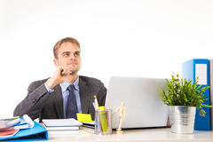 Young attractive businessman working busy with laptop computer holding pen thoughtful smiling Royalty Free Stock Photo