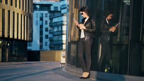 Young attractive businesswoman with cup of coffee is using smart phone in the city with office buildings.  stock video footage