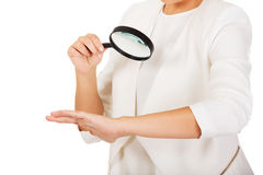 Young attractive businesswoman looking into a magnifying glass Stock Photo