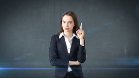 Young attractive businesswoman portrait in suit with standing and finger up,  studio background with copyspace. Royalty Free Stock Photos