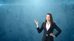 Young attractive businesswoman portrait in suit with standing and hand up,  studio background with copyspace. Stock Images