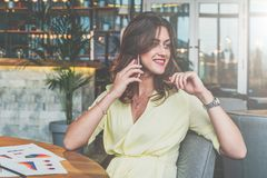 Young attractive businesswoman sitting alone at table in cafe and calling by cell phone. Royalty Free Stock Photos